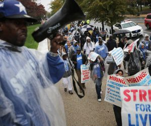 WASHINGTON, DC - NOVEMBER 10:  Demonstrators march along Constitution Avenue during a protest to call for higher wages for government contract workers on Capitol Hill November 10, 2015 in Washington, DC. Organized by Good Jobs Nation, the demonstrators were calling for a $15 per hour wage, plus benefits, for all U.S. federal contract workers, including many who work at the U.S. Capitol.  (Photo by Chip Somodevilla/Getty Images)